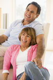 Couple in living room smiling Stock Photography
