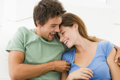 Couple in living room smiling Stock Photos
