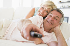 Couple in living room using remote control smiling Stock Photo