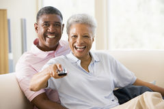 Couple in living room using remote control smiling Stock Photography