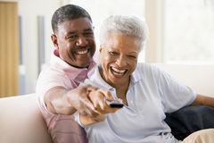 Couple in living room using remote control smiling Stock Images