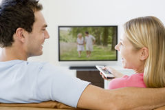 Couple in living room watching television Stock Photography