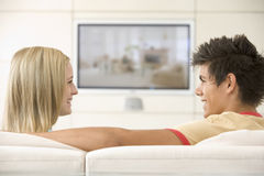 Couple in living room watching television smiling Stock Images