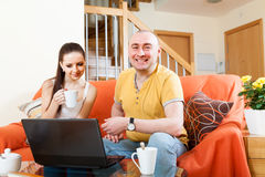 Couple in living room working at laptop. stock photography