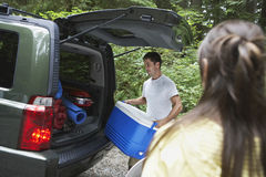 Couple Loading Car In Forest. Young men loading car in the forest royalty free stock photos