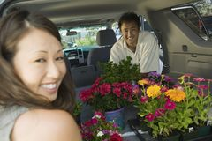 Couple Loading Flowers Into SUV Stock Photography