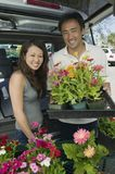 Couple Loading flowers into SUV stock image