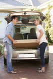 Couple Loading Large Package Into Back Of Car royalty free stock image