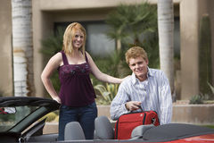 Couple Loading Luggage In Car. Portrait of a happy Caucasian couple loading luggage in convertible car Stock Image