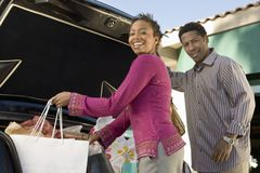 Couple Loading Shopping Bags In Car. Happy African American women with men loading shopping bags in car royalty free stock photos