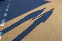 Couple long shadow holding hand on road trip. Couple shadow holding hand on road trip royalty free stock photos