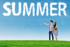 Couple look at cloud shaped summer text Royalty Free Stock Image