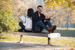 Couple Look At A Digtial Tablet And Book Stock Images