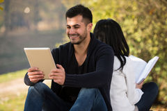 Couple Look At A Digtial Tablet And Book Stock Photo