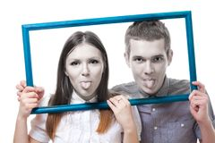 Couple look from frame with stick out tongue Stock Image