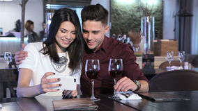 Couple look at smartphone at the restaurant. Caucasian couple looking at woman's white smartphone. Pretty girl showing something on her phone to brunette guy stock video footage
