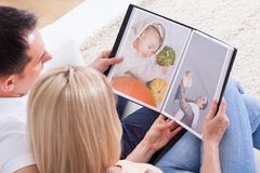 Couple Looking At Album. Portrait Of Couple Looking At Photo Album Stock Photography