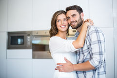 Couple looking away while embracing in kitchen Stock Photo