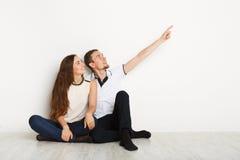 Couple looking away, sitting on floor Royalty Free Stock Image