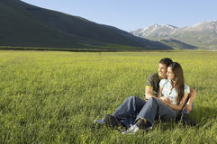 Couple Looking Away While Sitting On Grassy Field Stock Photos