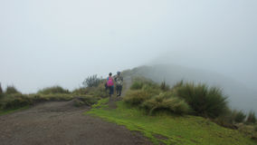 Couple looking backwards walking towards the summit of the Rucu Pichincha volcano on a cloudy day, near the city of Quito royalty free stock image