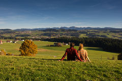 Couple looking at beautiful autumn landscape from Bavaria Germany. Couple looking at beautiful autumn landscape from Bavaria German,forest village view Stock Images
