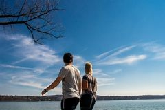 Couple looking at the beautiful lake scenery with clear blue sky background in Starnberg, Germany stock photo