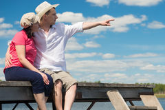 A couple looking at the beauty of nature. Two people sitting on the pier and look at nature Stock Image