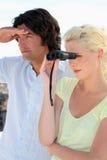 Couple looking through binoculars Royalty Free Stock Image
