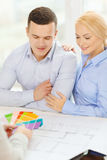 Couple looking at blueprint and color samples Stock Photos