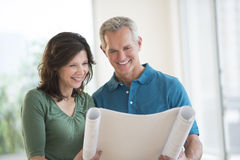 Couple Looking At Blueprint In New House. Happy mature couple looking at blueprint in their new house Stock Photography