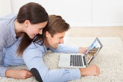 Couple looking at brandenburg gate on laptop at home Stock Photos