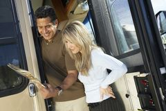 Couple Looking Through A Brochure. Happy couple at the entrance door of RV reading brochure Royalty Free Stock Photography