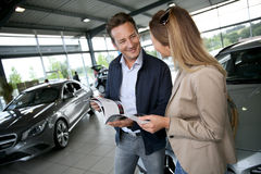 Couple looking at brochure buying new car in car shop Royalty Free Stock Image