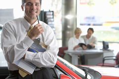 Couple looking at brochure in car showroom, focus on salesman in foreground, smiling, portrait Stock Photo