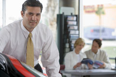 Couple looking at brochure in car showroom, focus on salesman in foreground, smiling, portrait Stock Photography
