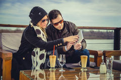 Couple looking at broken tablet. With river in background Royalty Free Stock Images
