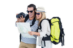 Couple looking in camera while carrying luggage Royalty Free Stock Photos