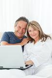 Couple looking at the camera at home Stock Images