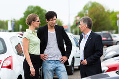 Couple looking at car on yard of dealer Royalty Free Stock Image