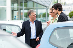 Couple looking at car on yard of dealer Stock Photography
