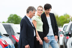 Couple looking at car on yard of dealer Royalty Free Stock Photography