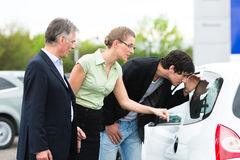 Couple looking at car on yard of dealer Stock Images