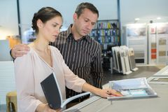 Couple looking at catalogue in store Stock Photography