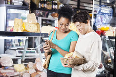 Couple Looking At Cheese Basket In Grocery Store Stock Photo