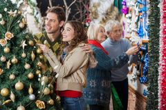 Couple Looking At Christmas Tree While Parents Stock Images