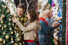 Couple Looking At Christmas Tree With Parents In Royalty Free Stock Images