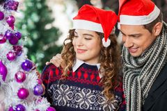 Couple Looking At Christmas Tree In Store Royalty Free Stock Photo