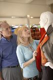 Couple Looking At Clothes In Clothing Store. Senior couple looking at clothes in clothing store Stock Photo