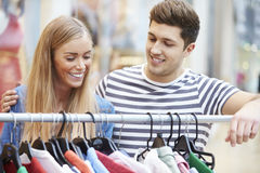Couple Looking At Clothes On Rail In Shopping Mall Royalty Free Stock Images